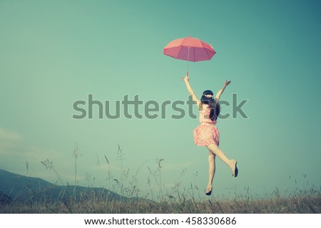Pink umbrella woman jump to sky.Summer Vacation Concept.Vintage Tone