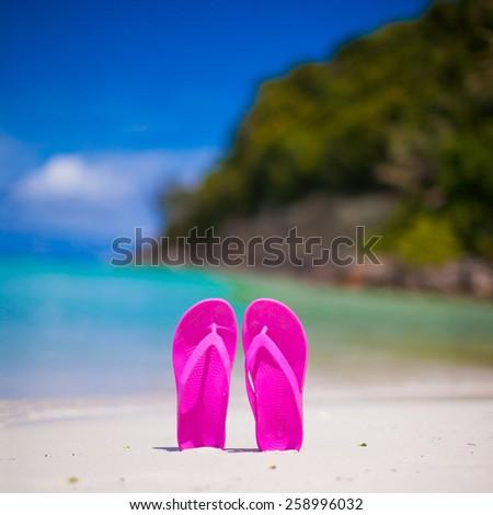 Pink vibrant beach flip flops on white sand on sea background - stock photo