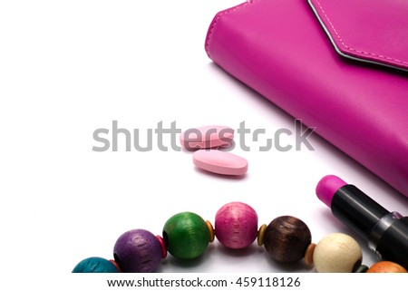 Pink vitamin tablets with magenta purse, lip stick and necklace on white background. Women health concept.