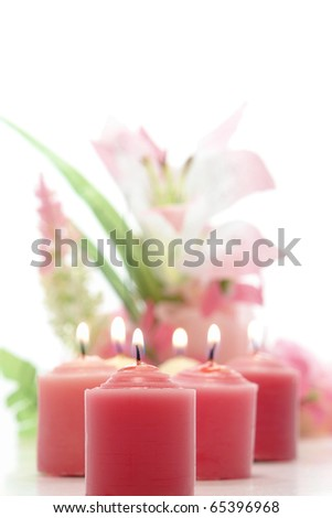 Pink votive candles softly burning before a pastel floral arrangement over white background