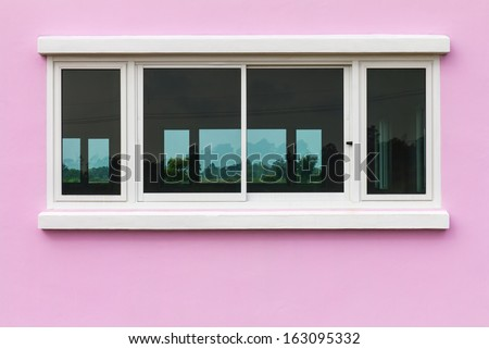 Pink walls and white opaque glass windows reflected trees in the scenic countryside. - stock photo