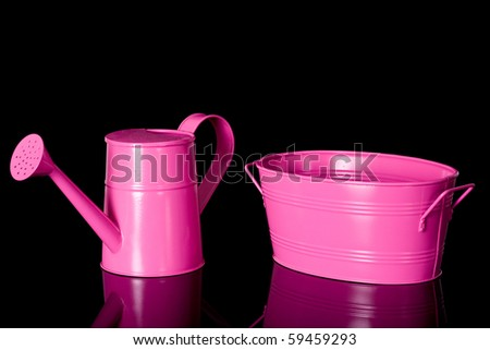 pink watering can and pink bowl, gardening set, studio shoot isolated on black with reflection - stock photo
