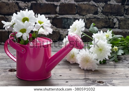 Pink watering can with white daisies on wooden table