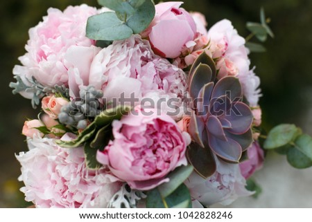 Pink wedding bouquet of peonies lying on the chair