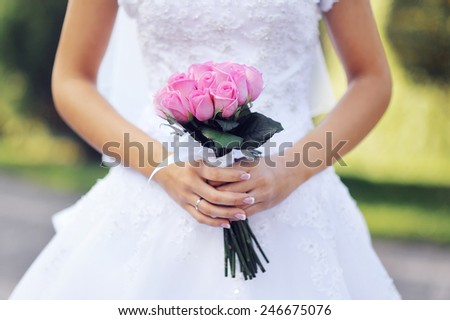 pink wedding bridal bouquet of roses in hands of the bride. - stock photo