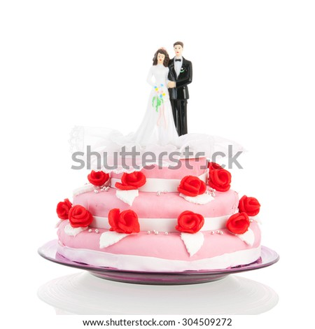 Pink wedding cake with red roses and couple on top - stock photo