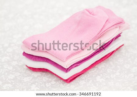Pink, white and purple pair of child socks on white background