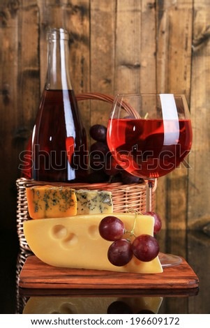 Pink wine, grapes and cheese on wooden background