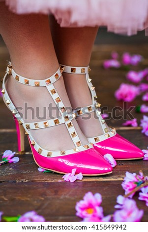 Pink women's shoes wearing on his feet on the wooden floor background with flowers. Macro - stock photo