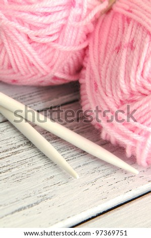 Pink woolen yarns and knitting needles