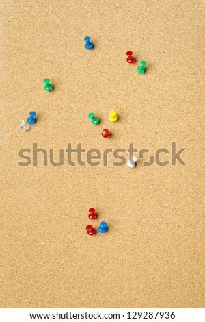 Pins stuck in surface of bulletin board with cork texture - stock photo
