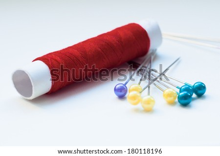 Pins with colourful heads and red thread isolated on white backg - stock photo