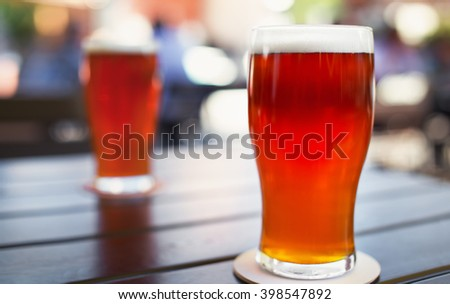 Pint glass of craft beer indian pale ale on wooden table in beer garden - stock photo