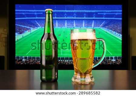 Pint of beer and bottle before tv showing soccer - stock photo