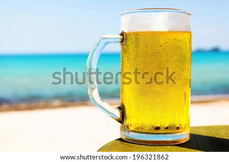 Pint of cold beer on top of the beach table. - stock photo