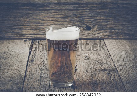 Pint of Pilsner Beer on Wood Background with Vintage Instagram Film Style - stock photo