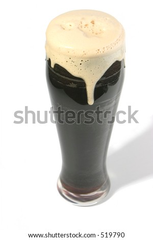 Pint of stout with creamy overflowing head. - stock photo