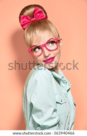 Pinup beauty woman in stylish glasses thinking, idea. Attractive funny blonde nerd girl smiling. Pinup hairstyle, trendy glasses, pinup bow and makeup. Unusual playful, expression.Vintage, on pink