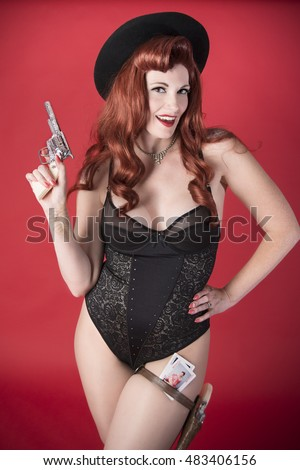 Pinup cowgirl with toy gun wearing cowboy hat