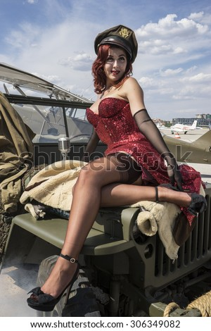 pinup dressed in era of the Second World War on a military jeep - stock photo
