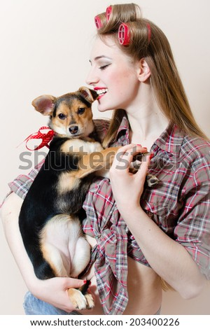 pinup girl beautiful blond young woman with curlers on her head having fun with little dog in her arms on white copy space background closeup portrait picture - stock photo