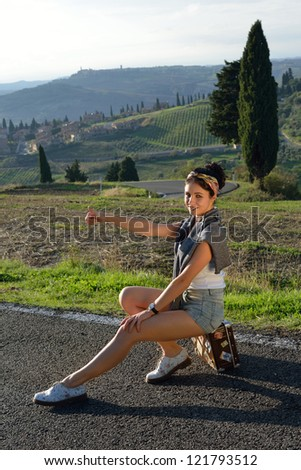 Pinup girl. Stylish hitchhiker young woman sits on the suitcase on a rural road at sunset time. Tuscan, Italy. - stock photo
