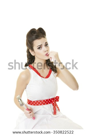 Pinup girl with her hair done in retro victory rolls, sucking on a finger she just banged with a hammer. - stock photo