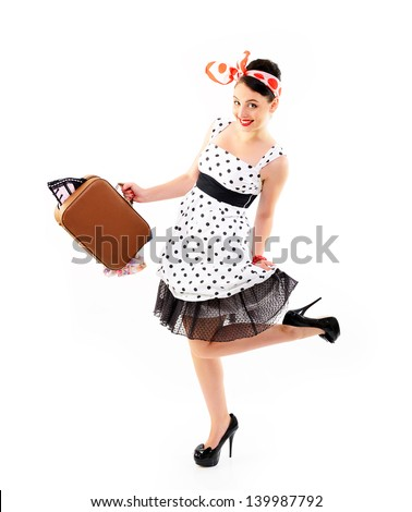 Pinup girl with suitcase in dress spotted, full length portrait of young happy sexy woman in pin-up style, retro stylization over white - stock photo