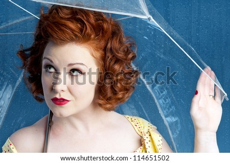 Pinup model holding an umbrella in rain