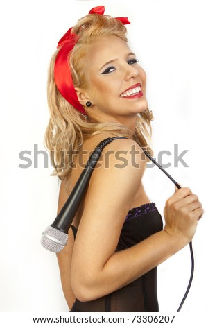 pinup style portrait of beautiful blond girl posing with microphone