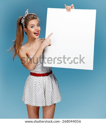 Pinup woman shows forefinger hand on the blank banner / photo set of young American pin-up model on blue background with space for text - stock photo
