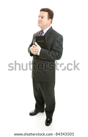 Pious minister or businessman holding his bible and looking thoughful.  Full body isolated on white. - stock photo