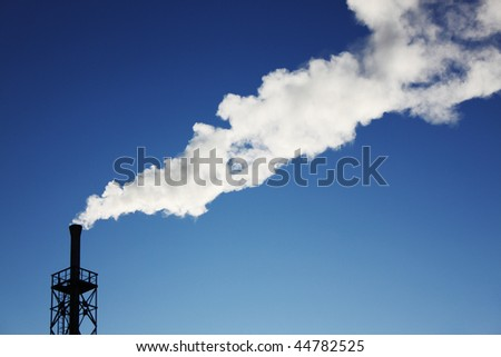 Pipe and white smoke against the dark blue sky