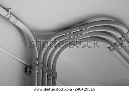 Pipe of electricity line on cement  wall in black and white tone