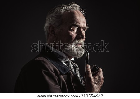 Pipe smoking vintage characteristic senior man with gray hair and beard. Studio shot against dark background. - stock photo