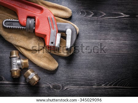Pipe wrench copper plumbing fixtures leather working gloves construction concept. - stock photo