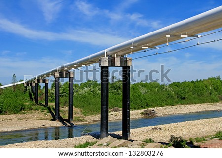 Pipeline transition through small river - stock photo