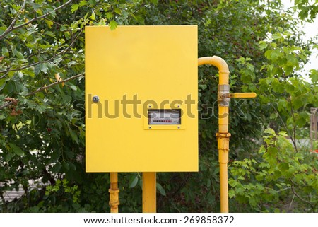 Pipes and gas-meter on nature background - stock photo