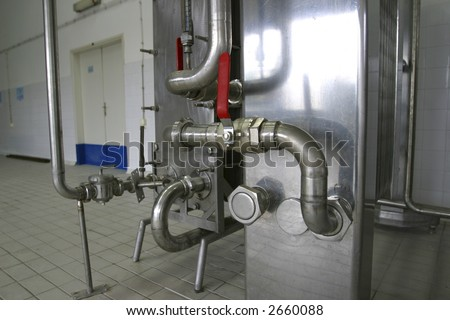 pipes and pressure valves  in dairy produce factory - stock photo