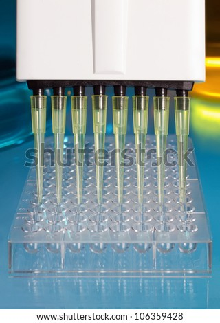 pipette depositing samples into a 96 well micro-plate