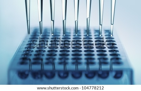 pipette dispensing samples in a deep well plate - stock photo