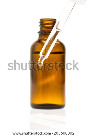 Pipette with drop in front of a bottle - stock photo