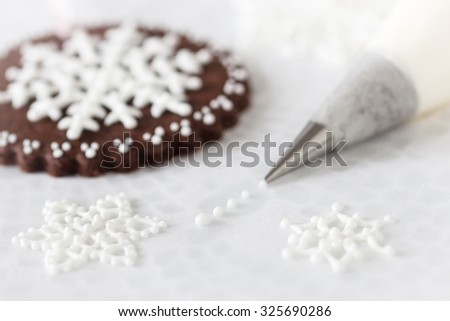Piping white snowflakes with royal icing, Selective focus. - stock photo