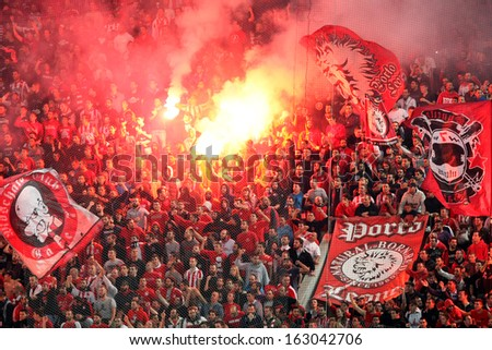 PIRAEUS, GREECE - NOV 10 : Fans of Olympiacos cheering for their team during the Greek Superleague match Olympiacos vs Paok on November 10, 2013 in Piraeus, Greece  - stock photo
