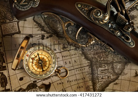 Pirate background. Ancient map and antique handgun and brass compass. - stock photo