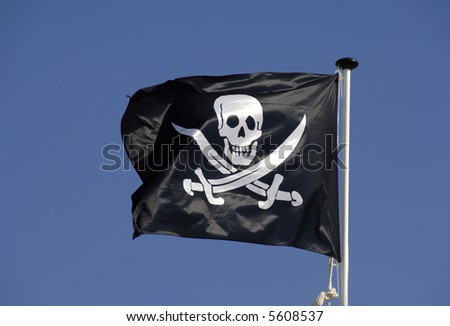 Pirate flag flying in blue sky skull and crossed bones - stock photo