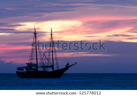 Pirate sailboat on sea navigating towards the sunset. The image was taken from Palm Beach in Aruba, in the Caribbean Sea.