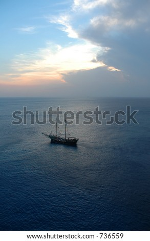 pirate ship on ocean at sunset - stock photo