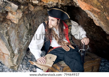 Pirate siting on treasure trunk - stock photo