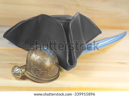 Pirate triangle hat and saber on the wooden background